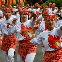Indonesian dancers perform the traditional Poco-poco dance in Jakarta on Sunday. At least 65,000 participants hoped to set a world record in their effort to promote the upcoming Asian Games. | AFP-JIJI