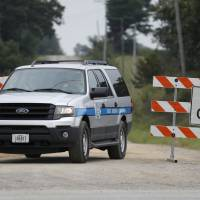 A State Medical Examiner vehicle passes through a barricade on a gravel road Tuesday near Brooklyn, Iowa. University of Iowa student Mollie Tibbetts was reported missing from her hometown in the eastern Iowa city of Brooklyn in July. | CHARLIE NEIBERGALL / VIA AP