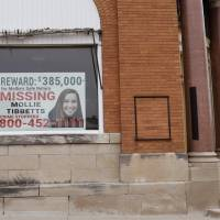 A poster for missing University of Iowa student Mollie Tibbetts hangs in the window of a local business, Tuesday in Brooklyn, Iowa. Tibbetts was reported missing from her hometown in the eastern Iowa city of Brooklyn in July. | CHARLIE NEIBERGALL / VIA AP