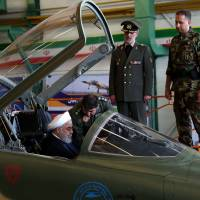 Iranian President Hassan Rouhani sits in the cockpit of the Kowsar domestically-made fighter jet at the National Defense Industry exhibition in Tehran on Tuesday. | AFP-JIJI / VIA IRANIAN PRESIDENCY