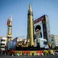 Missiles and a portrait of Iranian Supreme Leader Ayatollah Ali Khamenei are displayed in Tehran's Bharestan Square in September last year. | REUTERS
