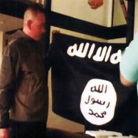 Army Sgt. 1st Class Ikaika Kang holds an Islamic State group flag after allegedly pledging allegiance to the terror group at a house in Honolulu last year. Kang pleaded guilty Wednesday as charged in an indictment last year, defense attorney Birney Bervar said. He is agreeing to a 25-year sentence for charges that could have put him in prison for life. | FBI/U.S ATTORNEY'S OFFICE, DISTRICT OF HAWAII / VIA AP