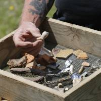A Jamestown Rediscovery Foundation archeologist shows artifacts and discusses what they know about one of the first enslaved Africans to live in English North America in Jamestown, Virginia, in April. | STEVE HELBER / VIA AP