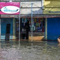A man bathes in floodwater in front of a grocery store and other shuttered businesses in Kainakary village in the district of Alappuzha, Kerala, in India, on Aug. 22. | BLOOMBERG