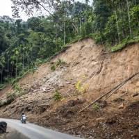 A motorcyclist and passenger ride along a road flanked by a hillside damaged by a landslide, at a coffee plantation near Munnar in the district of Idukki, Kerala, in India, on Aug. 25. Coffee production in India will slump to the lowest in 21 years next season after heavy rain, flooding and landslides damaged trees in the main growing areas in the south of Asia's third biggest producer. | BLOOMBERG