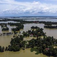Trees and houses are partially submerged in floodwaters in Kainakary village in the district of Alappuzha, Kerala, in India, on Aug. 23. | BLOOMBERG