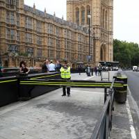 Apolice officer stands Wednesday at the vehicle barrier to the Houses of Parliament, where a car knocked down cyclists and pedestrians Tuesday. | REUTERS