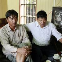 Doan Van Binh and Doan Van Thanh, the brother and father of Doan Thi Huong, talk to reporters at their house in the Vietnamese village of Nghia Binh in Nam Dinh province on Thursday.   AP