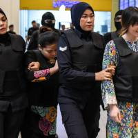 Vietnamese defendant Doan Thi Huong (right) and Indonesian defendant Siti Aishah (second, left) are escorted by Malaysian police personnel at the low-cost carrier Kuala Lumpur International Airport 2 in Sepang during a visit to the scene last year of the murder as part of the Shah Alam High Court trial process for their alleged role in the assassination of Kim Jong Nam. The two women accused of assassinating the half-brother of North Korea's leader in a brazen hit that shocked the world face a key court ruling on Thursday, with their families hopeful they will be acquitted and return home.   AFP-JIJI