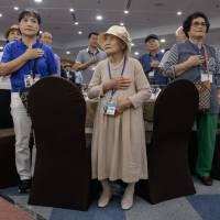 South Korean participants of the inter-Korean family reunions stand for the national anthem as they undergo a briefing on the eve of their departure for North Korea, at a hotel resort in Sokcho, South Korea, Sunday. | AFP-JIJI