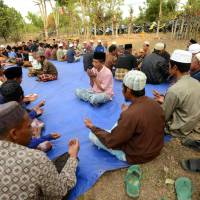 Villagers pray for earthquake victims in the Kayangan subdistict of North Lombok on Wednesday. | AFP-JIJI