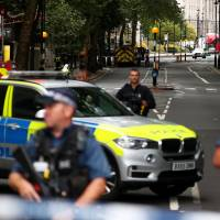 Armed police officers stand at a cordon after a car crashed outside the Houses of Parliament in Westminster, London, on Tuesday. | REUTERS