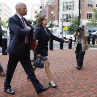 Jay Nanavati (left) with the defense team for Paul Manafort, walks with Manafort's wife, Kathleen Manafort, as they return to federal court during jury deliberations in the trial of the former Donald Trump campaign chairman, in Alexandria, Virginia, Monday. | JACQUELYN MARTI / VIA AP
