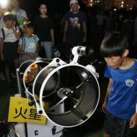 A boy looks at Mars through a telescope during a meeting of stargazers in Naha, Okinawa Prefecture, on Tuesday night. | KYODO