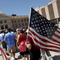 Members of the public line up to pay their respects to Sen. John McCain during a viewing at the Arizona Capitol on Wednesday in Phoenix.   MATT YORK / VIA AP