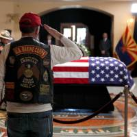 A former U.S. Marine pays his respects at the casket of U.S. Sen. John McCain during a memorial service at the Arizona Capitol on Wednesday in Phoenix.   JAE C. HONG / VIA AFP-JIJI