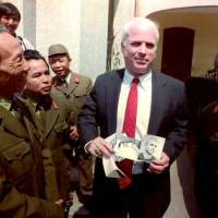 U.S. Sen. John McCain holds up photos of himself as a 30-year-old man wounded and captured in 1967 in North Vietnam, outside the Army Museum in Hanoi in October 1992. The photos were delivered by Col. Pham Duc Dai (left), director of the Army Museum, and Col. Tran Bien (right), representative on the missing in action issue at the Ministry of Defense, as a gift for visiting the museum. McCain, a celebrated war hero known for reaching across the aisle in an increasingly divided America, died Saturday after losing a battle with brain cancer. He was 81. | AFP-JIJI