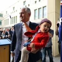 Australia's departing Prime Minister Malcolm Turnbull walks back with his granddaughter after a press conference in Canberra on Friday. Tresurer Scott Morrison was installed as Australia's seventh prime minister in 11 years on Friday after a stunning Liberal party revolt instigated by hard-line conservatives unseated moderate Malcolm Turnbull. | SAEED KHAN / VIA AFP-JIJI