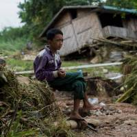 A flood victim sits near a house damaged by waters from the Swar Chaung dam in Swar, a township in Myanmar's Bago region, Thursday. | AFP-JIJI