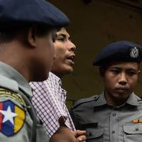 Reuters journalist Kyaw Soe Oo is escorted out of a court in Yangon on Monday.   AFP-JIJI