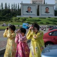 Women shield their faces from the sun as they cross a street in Pyongyang on July 27. | AFP-JIJI