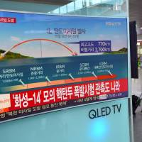 A man walks past a screen at a railway station in Seoul showing a news graphic of a North Korean missile launch over Japan in September. | AFP-JIJI