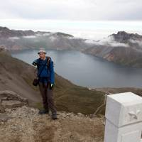 Tarjei Naess Skrede of Norway, who is hiking with Roger Shepherd of Hike Korea, stands near a view of the caldera and Lake Chon on Mount Paektu in North Korea on Saturday. | AP