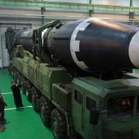 North Korean leader Kim Jong Un stands next to a Hwasong-15 intercontinental ballistic missile at an unidentified location in this photo released on Nov. 29. | AP