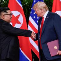 U.S. President Donald Trump and North Korean leader Kim Jong Un shake hands during the signing of a document after their summit in Singapore on June 12. | REUTERS