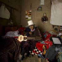 In this Aug. 23 photo, 117-year-old Julia Flores Colque holds a 'charango,' a small Andean stringed instrument, at her home in Sacaba, Bolivia. Flores Colque still sings in her indigenous Quechua tongue and strums the five strings of her tiny Andean guitar. | JUAN KARITA / VIA AP