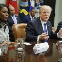 U.S. President Donald Trump is flanked by then-White House staffer Omarosa Manigault Newman (left) as he speaks during a meeting on African American History Month in the Roosevelt Room of the White House on Feb. 1, 2017.   AP