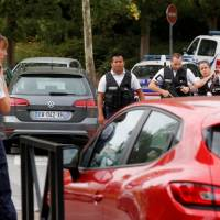 French police secure a street on Aug. 23 after a man killed two persons and injured another in a knife attack in Trappes, near Paris, according to French authorities. | REUTERS