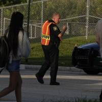 A Broward sheriff deputy watches as students arrive at Marjory Stoneman Douglas Wednesday on the first day of school. Broward County Public Schools Superintendent Robert Runcie said Wednesday that the start of a new school year at Marjory Stoneman Douglas High School in Parkland is 'a challenging time' for students, teachers and other school employees. | JOE CAVARETTA / SOUTH FLORIDA SUN-SENTINEL / VIA AP