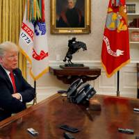 U.S. President Donald Trump answers a reporter's question as eight different phones and recording devices placed on his desk by reporters and White House staff record his words during an interview with Reuters in the Oval Office of the White House in Washington Monday. | LEAH MILLIS / VIA REUTERS