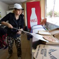 An employee of pizzeria 'Pizza Veterano' prepares pizza to be delivered to the frontline for Ukrainian servicemen fighting against Russian-backed separatists, on July 18, 2018 in Mariupol. | AFP-JIJI