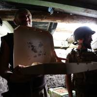 Ukrainian servicemen who fight against Russian-backed separatists hold a box with pizza delivered to the frontline by Aleksey Kachko, co-owner of small pizzeria 'Pizza Veterano' in Mariupol, on July 19, 2018. | AFP-JIJI