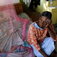 Aurea Cruz, 66, sits on her bed inside her house damaged by Hurricane Maria in Vieques, Puerto Rico, last November. Hurricane Maria killed 2,975 people in Puerto Rico, according to the results of a long-awaited study commissioned by the U.S. government, amid controversy over the true toll of the 2017 storm. 'The results of our epidemiological study suggest that, tragically, Hurricane Maria led to a large number of excess deaths throughout the island,' said principal investigator Carlos Santos-Burgoa, a professor of global health at George Washington University. | RICARDO ARDUENGO / VIA AFP-JIJI