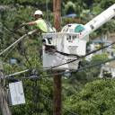 A worker from the Cobra Energy Company, contracted by the Army Corps of Engineers, installs power lines in the Barrio Martorel area of Yabucoa, Puerto Rico, in May. Officials said on Tuesday that the power has been restored to the entire island for the first time since Hurricane Maria struck nearly 11 months ago.