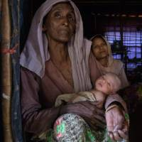 Twenty-year-old Rohingya refugee Setara (right) sits behind her 8-day-old baby and her mother-in-law, Sokhina Khatun, at the Thangkhali refugee camp near Cox's Bazar on Aug. 11. Setara, who arrived in Bangladesh in September 2017, gave birth with the help of a neighboring midwife from the same village where she lived in Myanmar. | AFP-JIJI