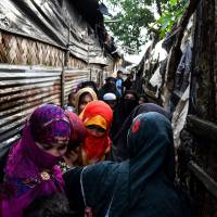 Rohingya family members gather around the bride (left) as she enters the groom's home as a part of religious ceremony during marriage celebrations in the Kutupalong refugee camp near Cox's Bazar on Aug. 10. | AFP-JIJI