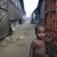 A Rohingya Muslim child stands outside a shelter at the Thet Kel Pyin camp in Myanmar's Rakhine state during the Eid al-Adha celebrations on Wednesday. | AFP-JIJI