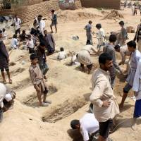 Yemenis dig graves on Friday for children killed when their bus was hit during a Saudi-led coalition air strike the previous day in the Huthi rebels' stronghold province of Saada. | AFP-JIJI