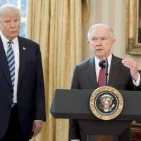 U.S. President Donald Trump stands alongside newly sworn-in Attorney General Jeff Sessions in the Oval Office of the White House on Feb. 9, 2017. | AFP-JIJI