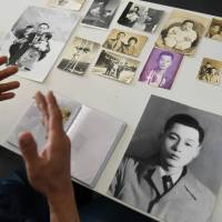 Hwang In-cheol displays old photos of his father in Seoul on Thursday. | AFP-JIJI