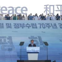South Korean President Moon Jae-in delivers a speech below characters and letters reading 'Peace' during a ceremony marking the 73rd anniversary of the end of Japanese colonial rule in 1945, at the National Museum of Korea in Seoul on Aug. 15. | AFP-JIJI