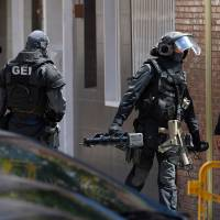 Special police leave after searching the apartment of a man who tried to attack a police station in Cornella near the northeastern Spanish city of Barcelona on Monday. | LLUIS GENE / VIA AFP-JIJI