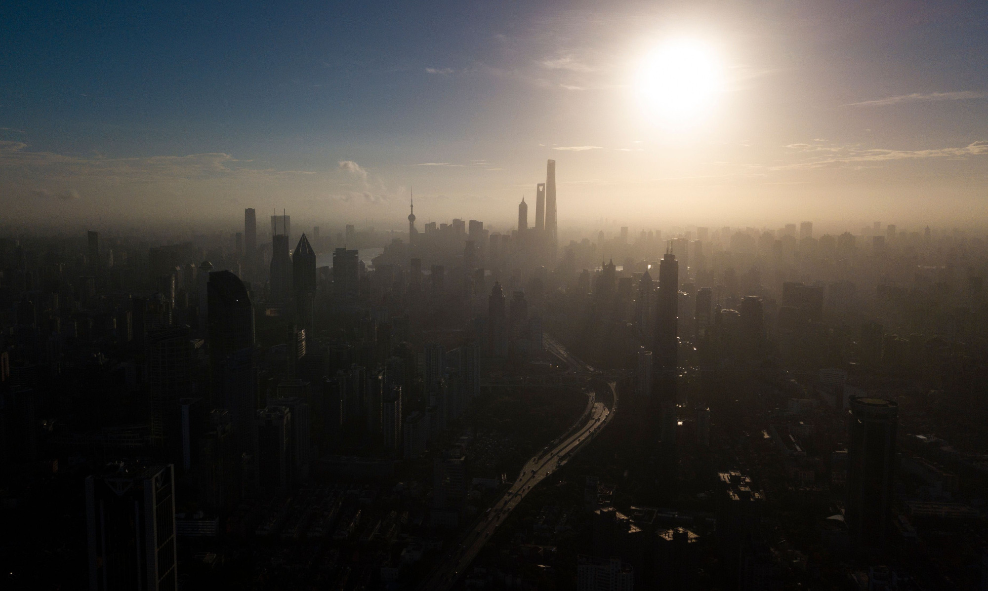 The sun rises over the financial district of Pudong in Shanghai on Monday. To catch up with the U.S., China will have to avoid the middle-income trap that keeps many emerging economies stuck with a per capita GDP of around $15,000. | AFP-JIJI