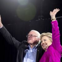 Then-U.S. Democratic presidential candidate Hillary Clinton and Sen. Bernie Sanders appear on stage at a rally in Raleigh, North Carolina, in November 2016.   AP