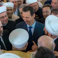 Syrian President Bashar Assad greets supporters during Eid al-Adha prayers at a mosque in Damascus on Tuesday. | REUTERS
