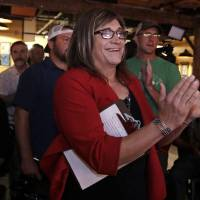 Vermont Democratic gubernatorial candidate Christine Hallquist, a transgender woman and former electric company executive, applauds with her supporters during her election night party in Burlington, Vermont, Aug. 14. Vermont's incumbent governor says he's saddened to hear that his opponent in the November election has been getting a steady stream of death threats and other personal attacks since her candidacy began to gain traction. Republican Gov. Phil Scott made the comments Tuesday after his Democratic opponent, Hallquist, the nation's first openly transgender person to win a major party nomination to run for governor, reported the threats. | CHARLES KRUPA / VIA AP